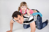 Llittle cute daughter lies on back of his father and waves hand — Stock Photo