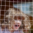 Stock Photo: Little beautiful happy girl shouts in green playground with grid