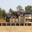 Brick country house and unfinished wooden building over brown fe — Stockfoto