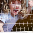 Stock Photo: Little beautiful happy girl shouts at playground with grid.