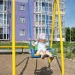 Little girl sits on yellow swing at playground near violet build — Stock Photo