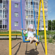 Little girl sits on yellow swing at playground near violet build — Stock Photo #33941695