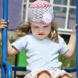 Little happy girl sits on swing at playground violet building at — Stock Photo