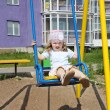 Little cute girl sits on swing at playground near building at su — Stock Photo