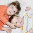 Little brother and pretty sister lie on white sheet on bed and l — Stock Photo