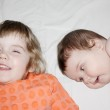 Little brother and pretty sister smile and lie on white sheet on — Stock Photo #33942041