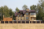 Brick country house and unfinished wooden building over brown fe — Stock Photo