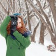 Beautiful girl holds photographs by retro camera at winter day i — Stock Photo