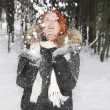 Girl in hood with fur throws up snow in the woods at winter. — Stock Photo