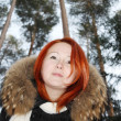 Happy redhead girl looks at camera in pine forest at winter. — Stock Photo