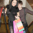 Stock Photo: Young beautiful girl and boy rise on escalator with shopping bag