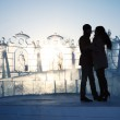 Silhouette of young couple near ice wall with sculptures at wint — Stock Photo
