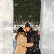 Girl kisses boy in ice arch near big Christmas tree at winter da — Stock Photo #38447151