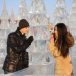 Young couple stand near ice spruce in ice forest and look at eac — Stockfoto