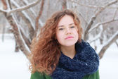 Pretty curly girl in green looks at camera outdoor at winter day — Foto Stock
