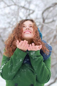 Pretty girl catches snow by palms and looks up at winter day in — Stock Photo