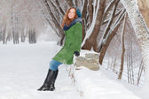 Beautiful girl in green overcoat poses outdoor at winter day in — Stock Photo