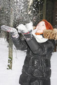 Happy girl in black jacket throws up snow in woods at winter. — Stockfoto