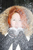 Happy girl in black jacket blows on snow in woods at winter. — Stockfoto
