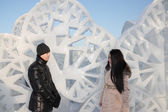 Young boy and girl stand near ice wall with triangular holes an — Foto de Stock