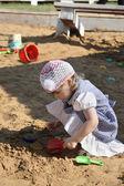 Dziewczynka w strój odgrywa w piaskownicy z łopatą na letnie dni. — Zdjęcie stockowe