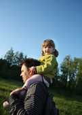 Happy little daughter sits on shoulders of her father outdoors. — Stock Photo