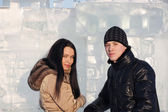 Young beautiful couple stand neat ice wall at sunny winter day. — Foto de Stock