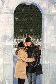 Girl kisses boy in ice arch near big Christmas tree at winter da — Stock Photo