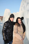 Young happy boy and girl stand near big ice wall at winter day. — Stok fotoğraf