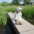 Pretty little girl sits on small bridge in village at summer sun — Stock Photo