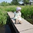 Pretty little girl sits on small bridge in village at summer sun — Stock Photo