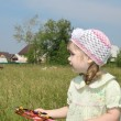 Little girl with windmill looks away at meadow near village at s — Stock Photo