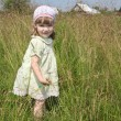 Pretty little girl in dress stands among high grass at meadow at — Stock Photo