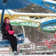 Stock Photo: Beautiful girl sits on old carousel outdoor at winter day in par