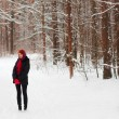 Pretty young girl stands and looks away at winter day in forest — Stock Photo