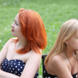 Stock Photo: Two beautiful girls sit on bench and take offense at each other