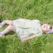 Cute little girl with closed eyes lies on grass of green meadow — Stock Photo