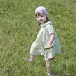 Pretty little girl in dress with flowers walks at meadow at summ — Stock Photo