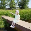Pretty little girl sits, shows thumb and wonders on small bridge — Stock Photo