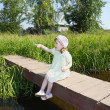 Pretty little girl sits, shows thumb and wonders on small bridge — Stock Photo #39489261