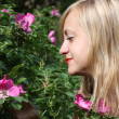 Beautiful blonde girl looks at pink flowers on bush in park at s — Stock Photo #39489279