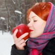 Pretty girl in red kerchief holds big red apple outdoor at winte — Stock Photo #39489369