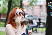 Beautiful girl in sunglasses blows bubbles in park at summer day — Stock Photo