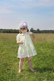 Little barefoot girl plays with camomile at green meadow at summ — Stock Photo