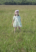 Cute little girl in dress stands at green meadow at summer sunny — Stock Photo