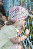 Little pretty girl looks through blue grid at summer sunny day — Foto Stock