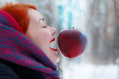 Smiling girl and hanging in air big red apple outdoor at winter — Stock Photo