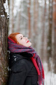 Smiling girl stands next to tree and looks up outdoor at winter — Stock Photo