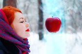 Smiling girl looks at hanging in air big red apple outdoor at wi — Stock Photo