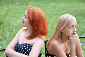 Two beautiful girls sit on bench and take offense at each other — Stock Photo
